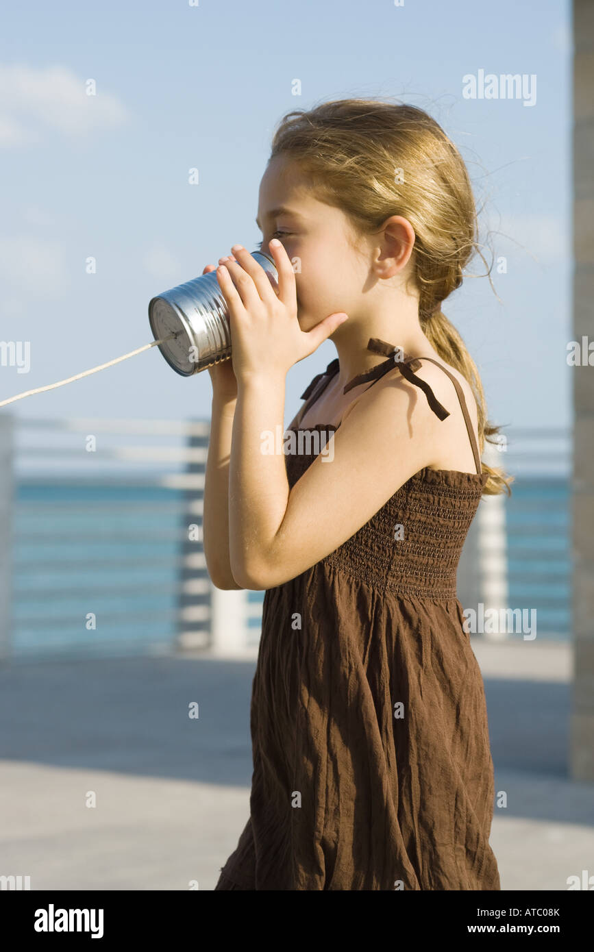Little girl talking into tin can phone, side view - Stock Image
