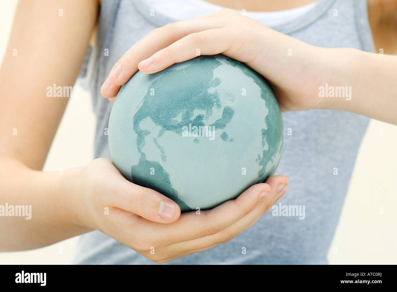 Woman holding globe in cupped hands, close-up, cropped view - Stock Image