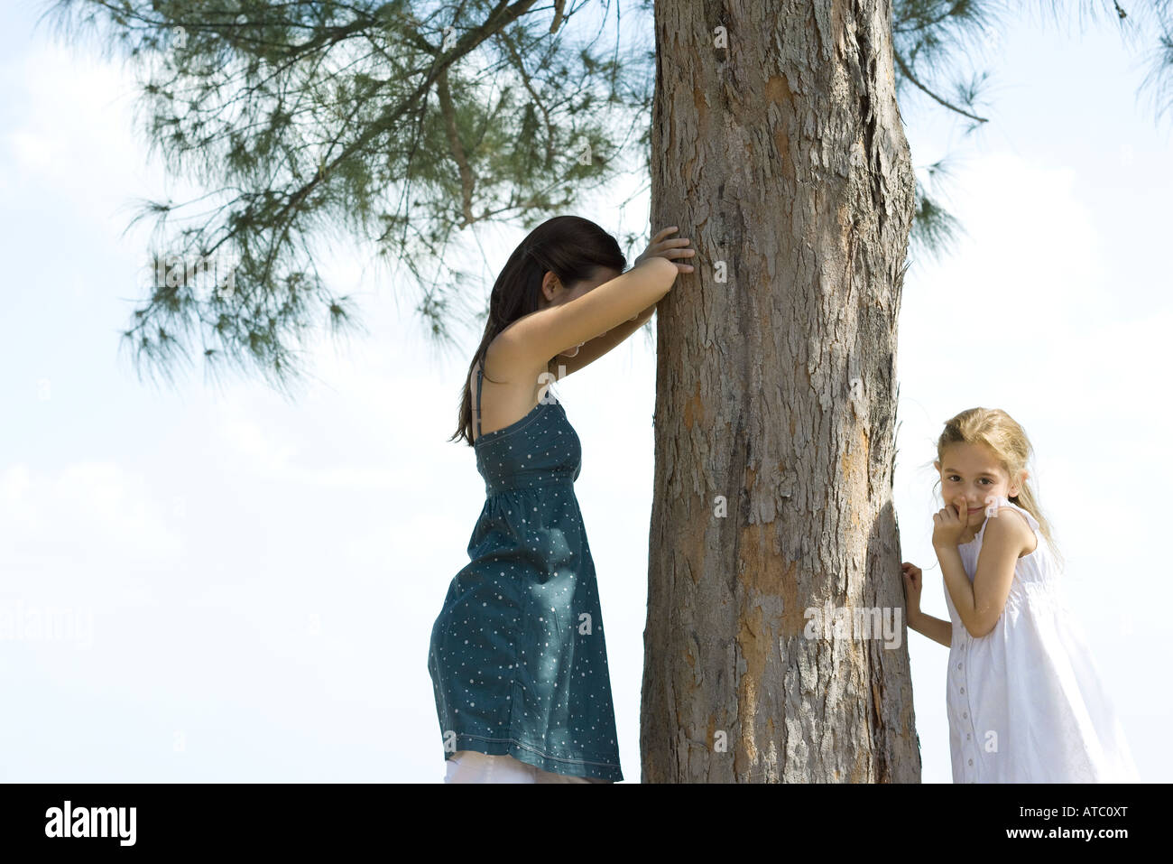 Two young friends playing hide-and-seek, one placing finger on lips and looking at camera - Stock Image