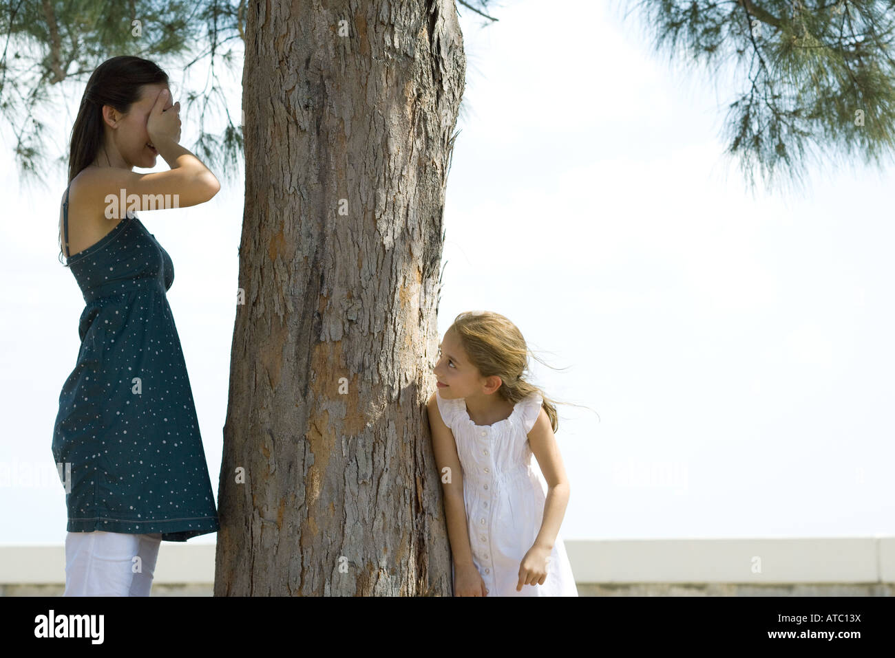 Two sisters playing hide-and-seek together, one covering eyes with her hand - Stock Image
