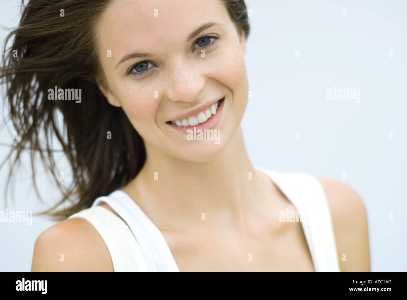 Teenage girl smiling at camera, hair tousled by breeze, portrait - Stock Image