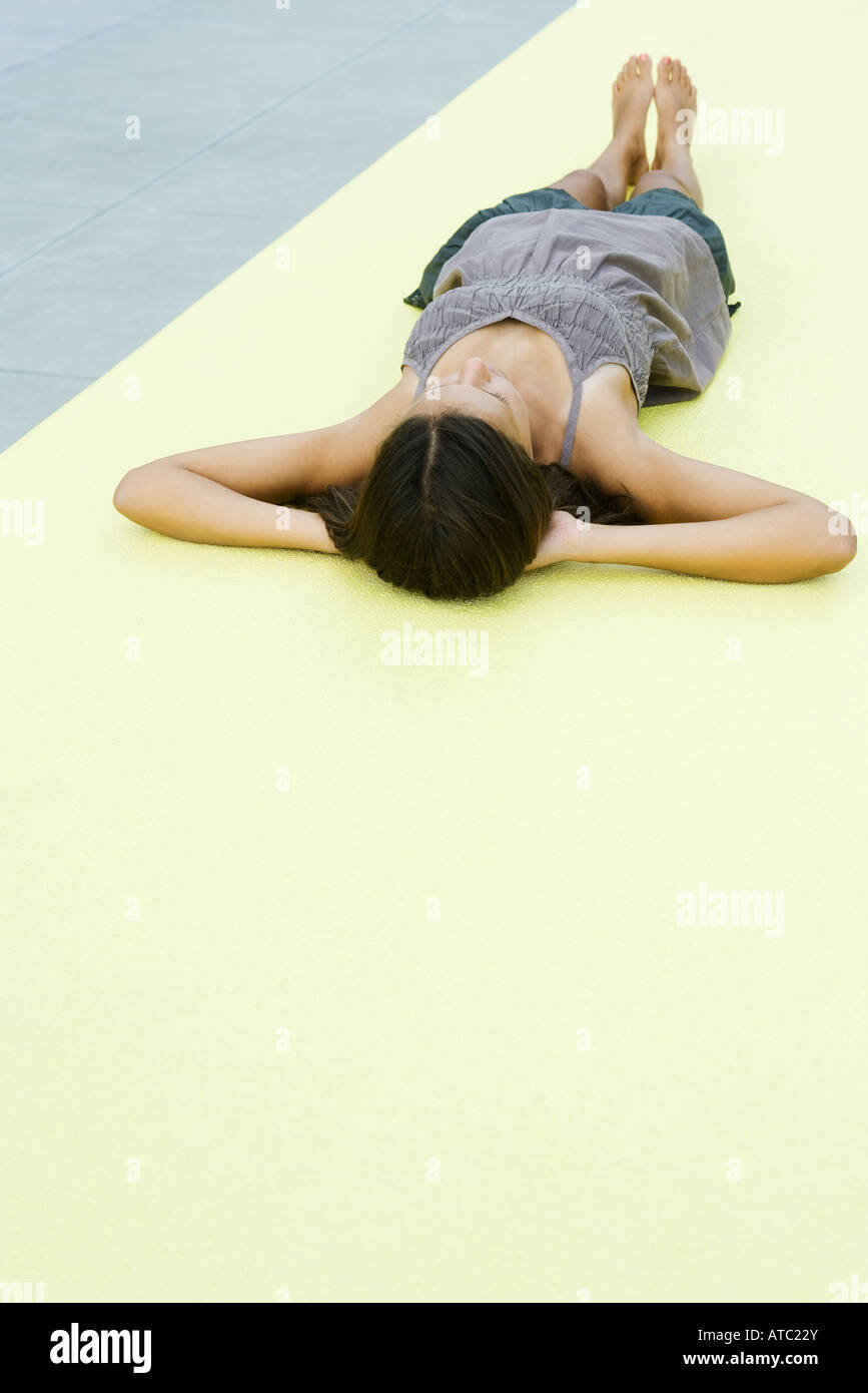 Teenage girl lying on the ground with hands behind head - Stock Image