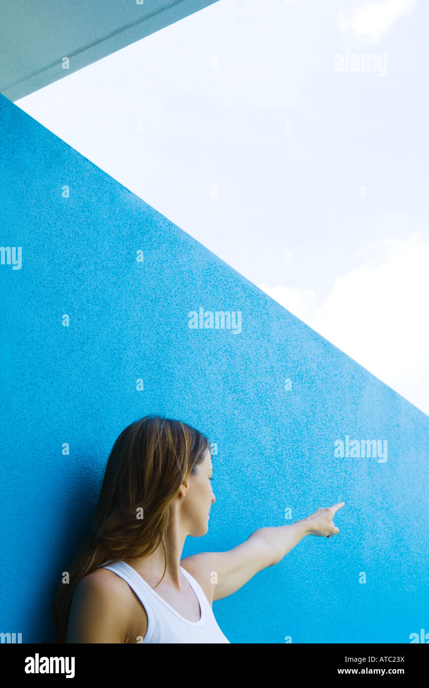 Female in front of blue wall, pointing, looking away - Stock Image