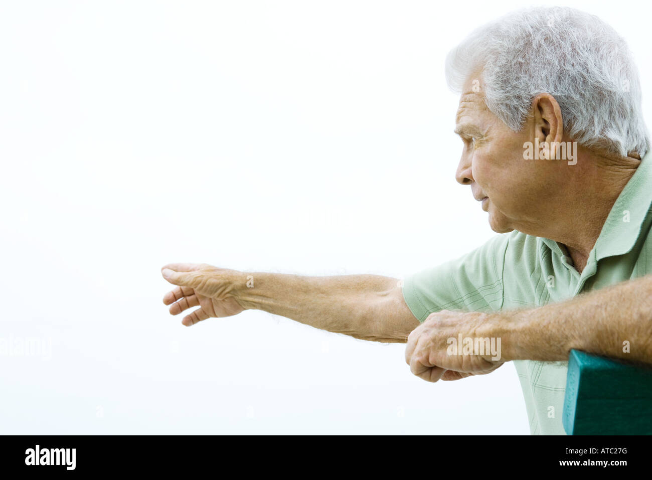 Senior man pointing, looking away, side view - Stock Image