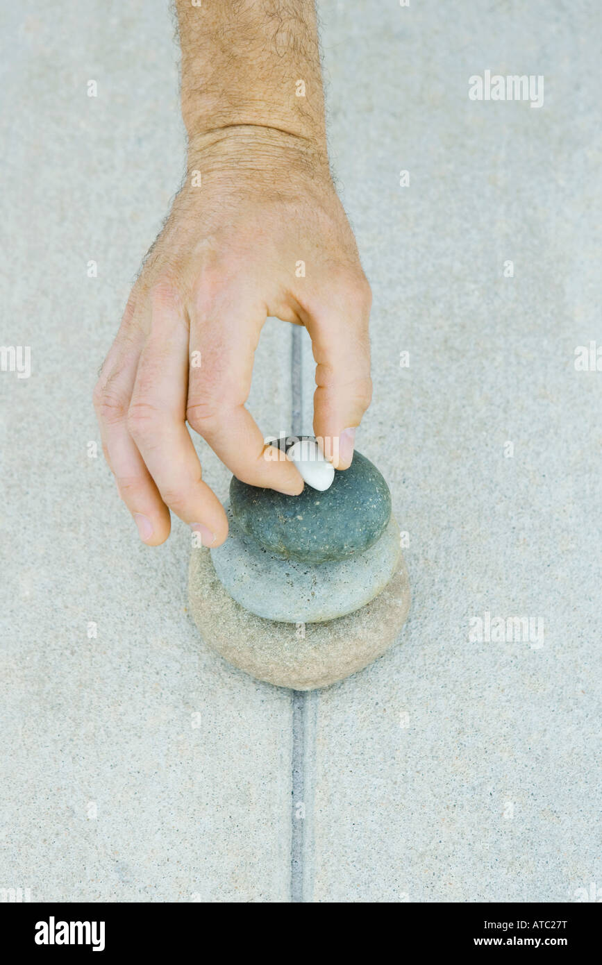 Man stacking pebbles, cropped view of hand - Stock Image