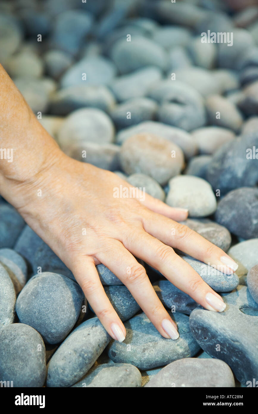 Woman touching pebbles, cropped view of hand - Stock Image