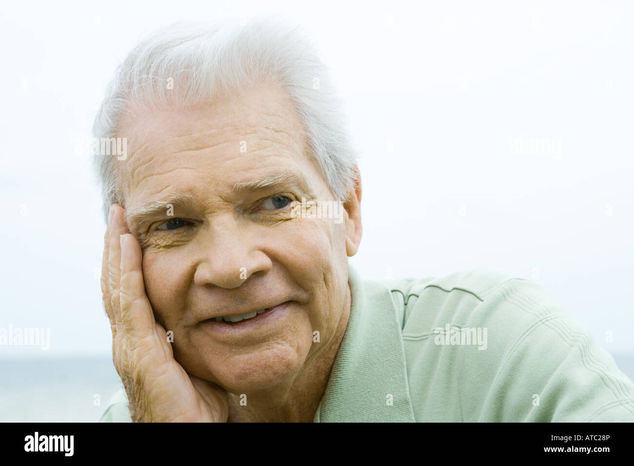 Senior man with hand on cheek, smiling, looking away - Stock Image