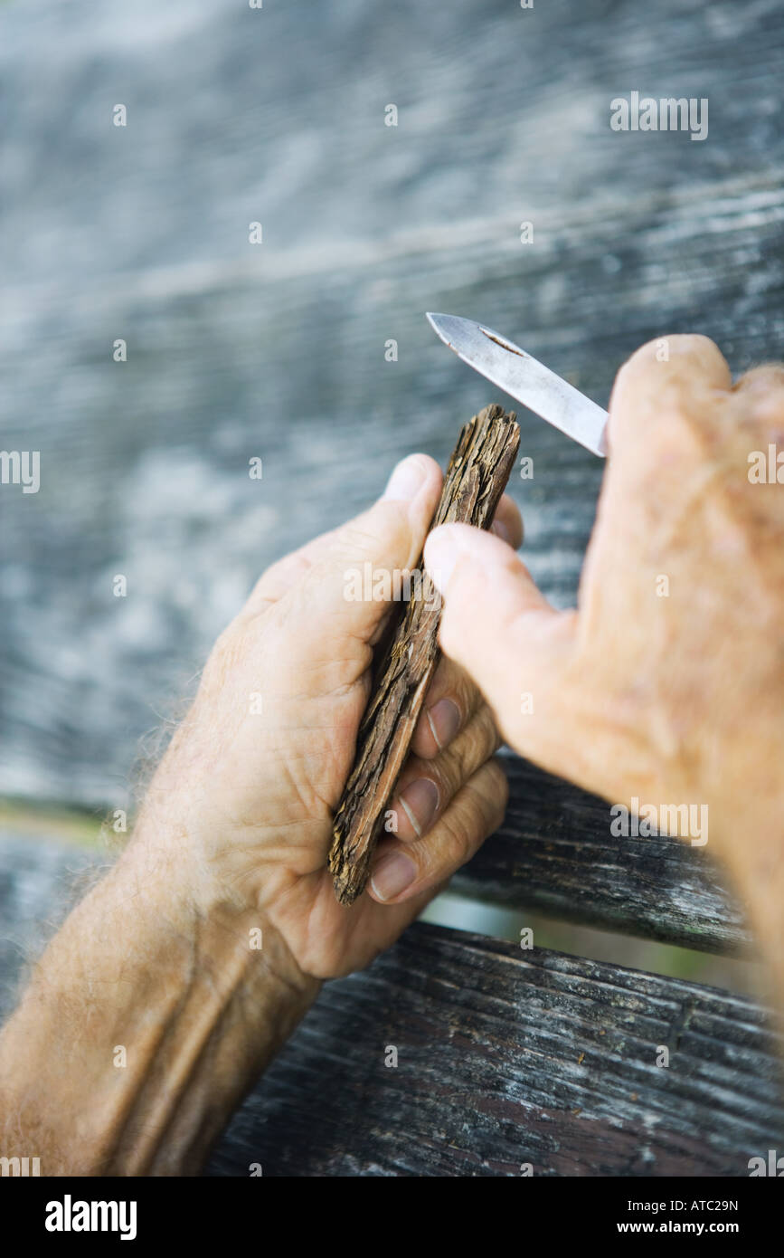 Man carving wood with knife, cropped view of hands - Stock Image