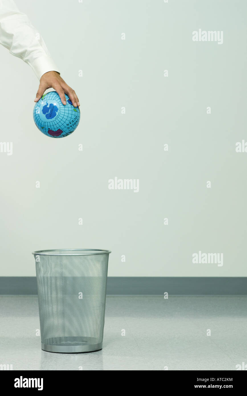 Businessman holding globe over trash can, cropped Stock Photo