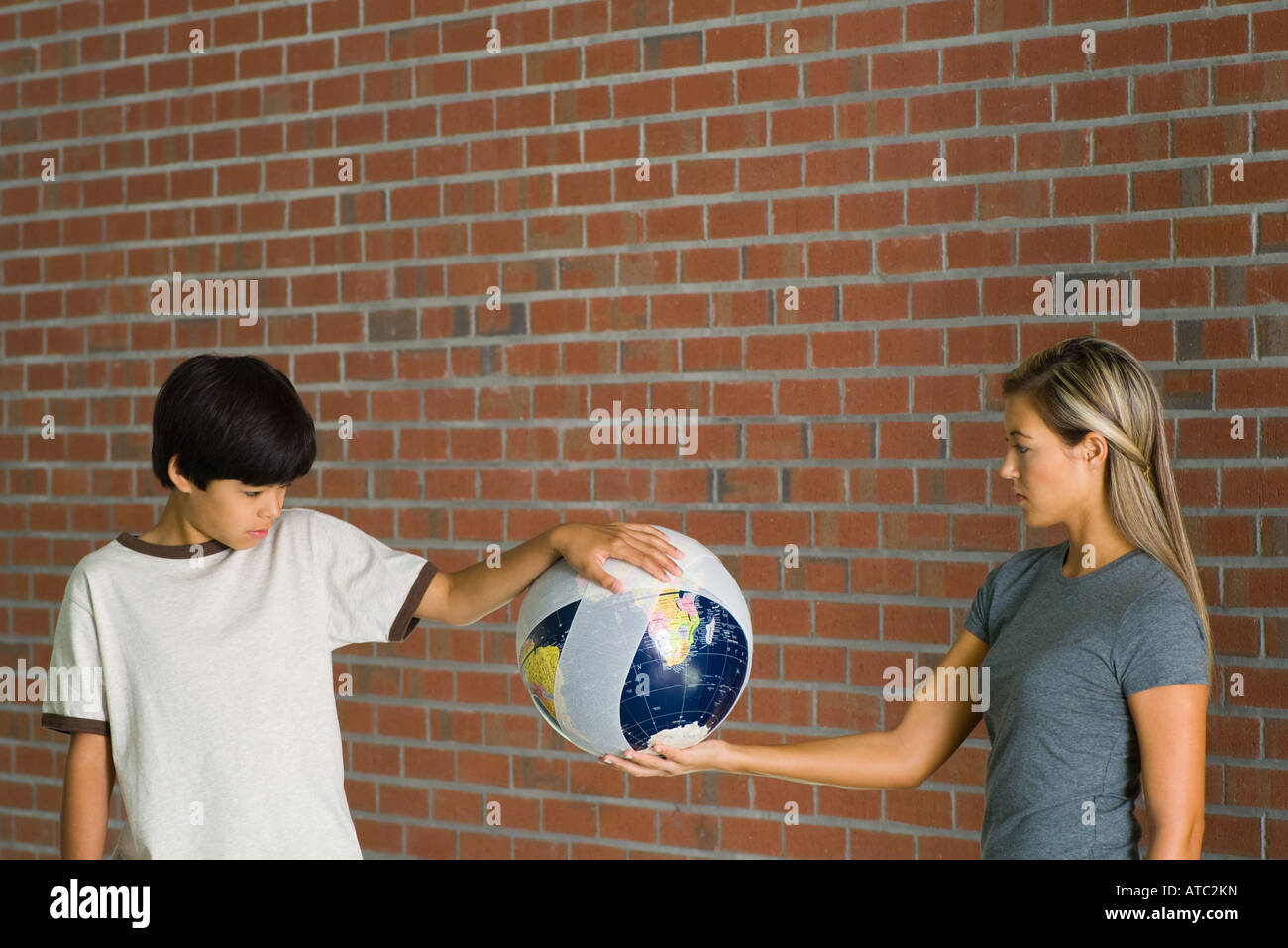Boy and woman holding bandaged globe together - Stock Image