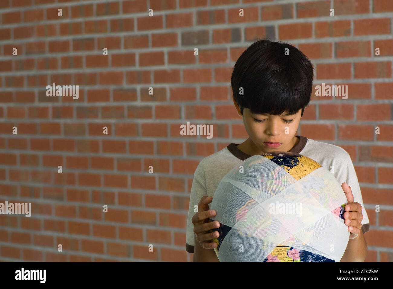 Boy holding bandaged globe, front view - Stock Image