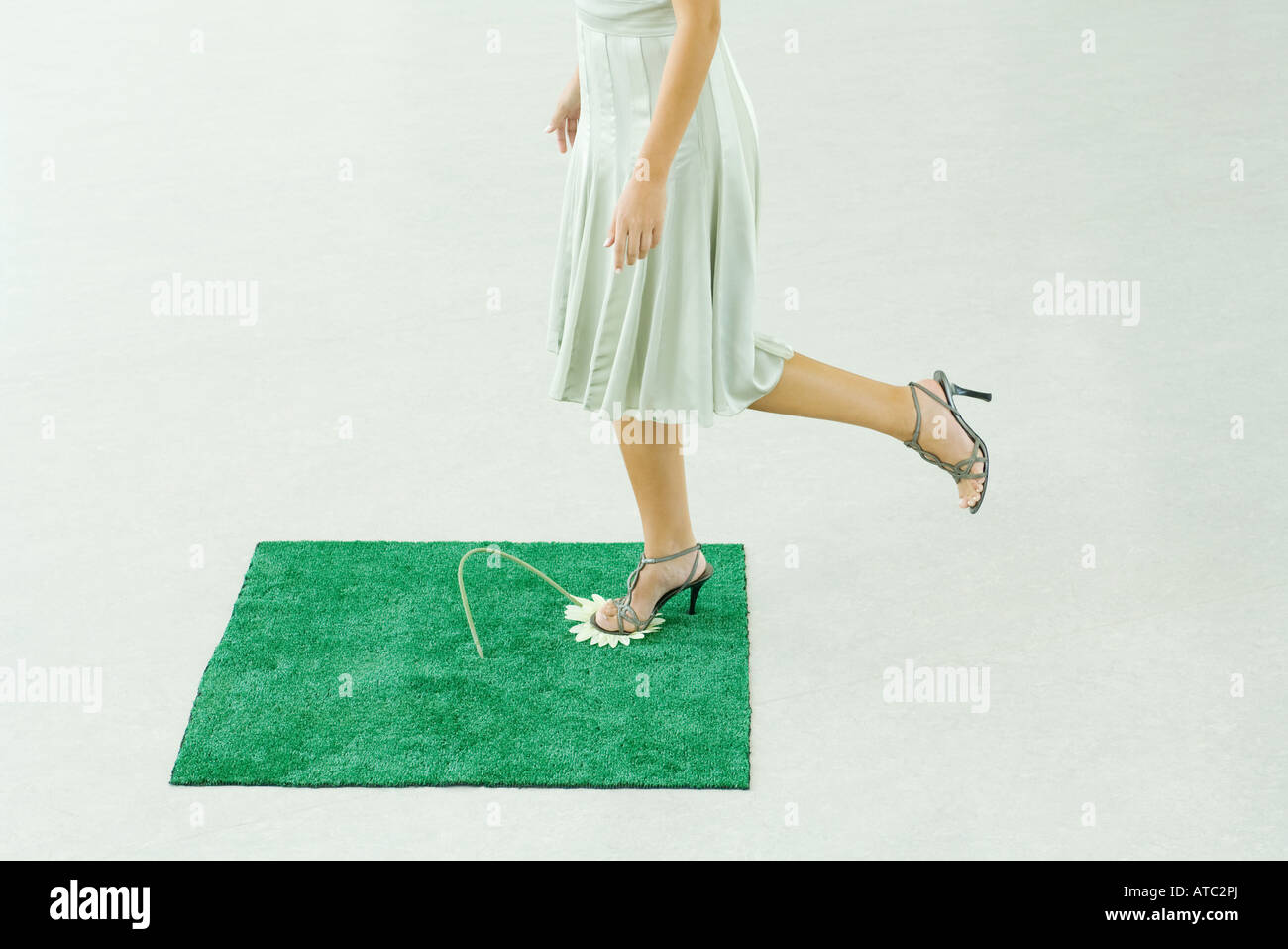 Woman stepping on flower in square of artificial turf, waist down - Stock Image