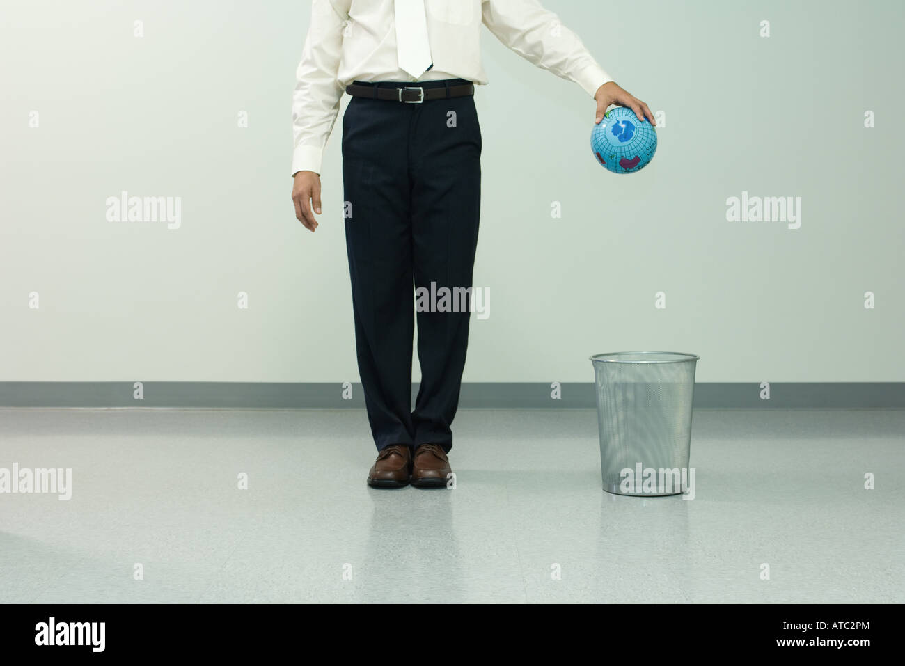 Businessman holding globe over trash can, chest down, front view - Stock Image