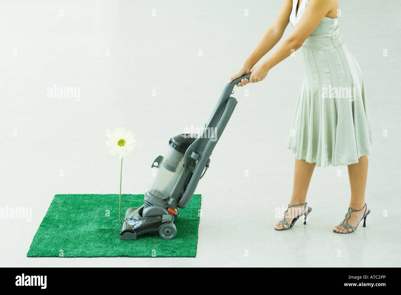 Woman vacuuming square of artificial turf, chest down - Stock Image