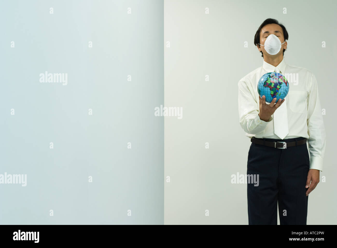 Businessman wearing pollution mask, holding out globe, eyes closed, front view - Stock Image