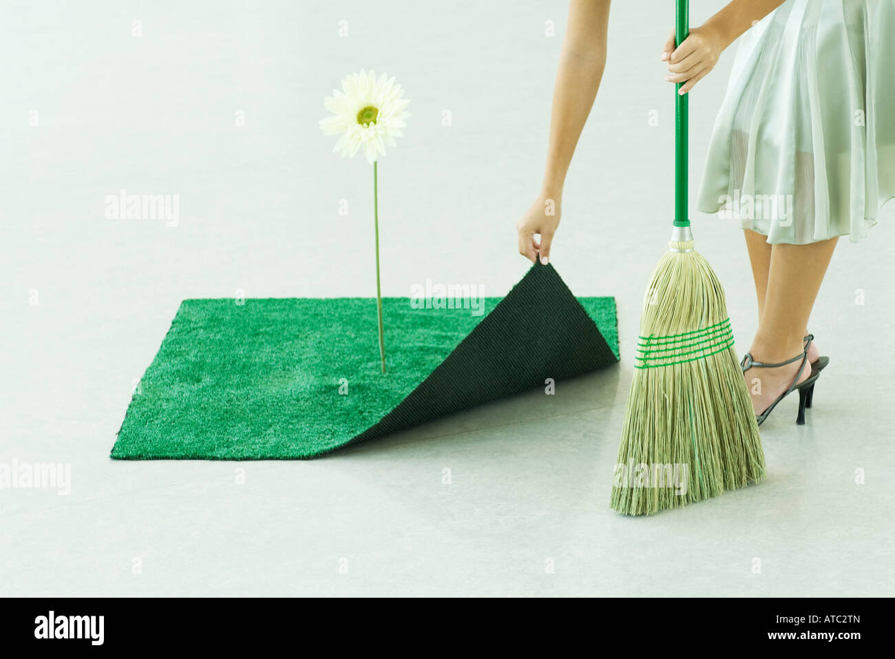 Woman sweeping under artificial turf rug, waist down - Stock Image