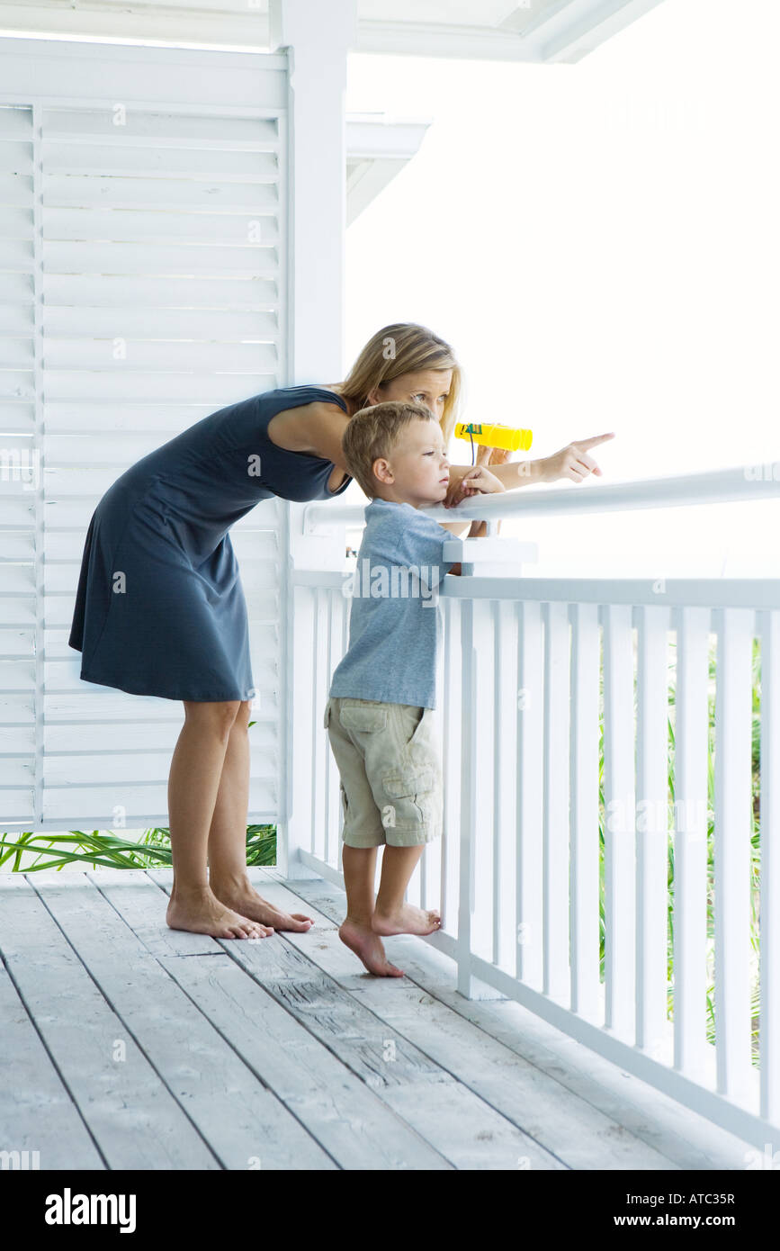 Mother and son standing on porch together, woman holding binoculars and pointing, both looking away - Stock Image