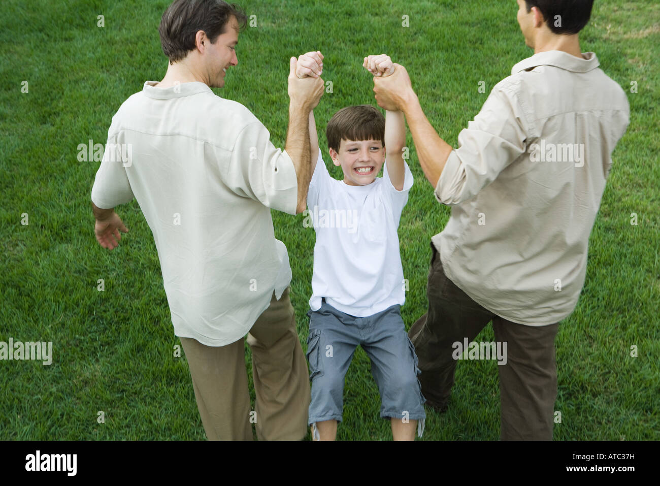 Two men carrying boy by his arms, high angle view - Stock Image