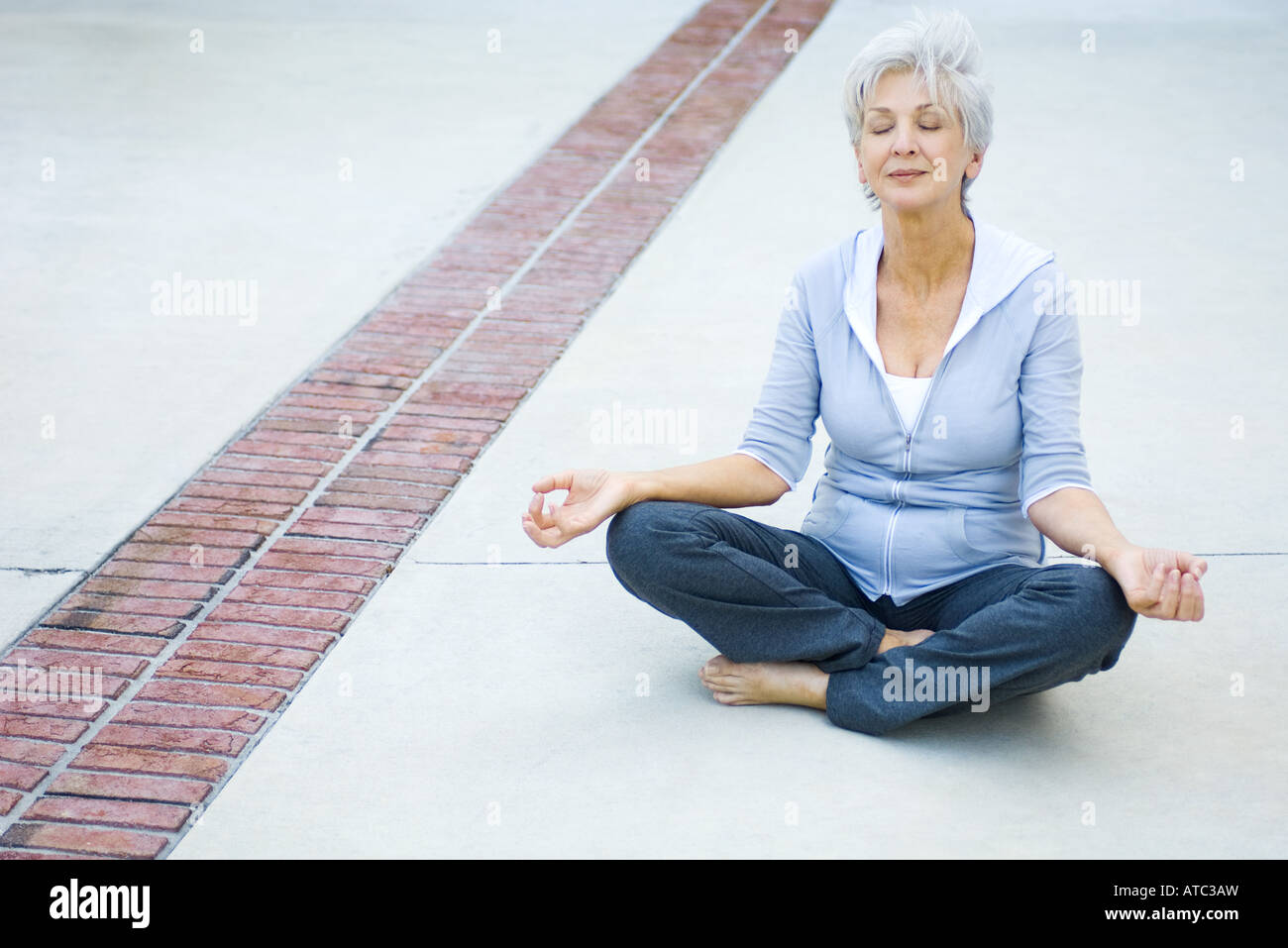 Senior woman sitting in lotus position, eyes closed - Stock Image