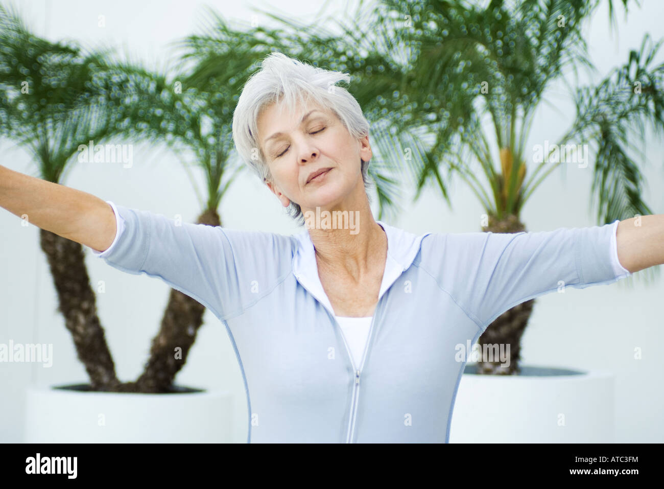 Senior woman with arms outstretched, head tilted, eyes closed - Stock Image