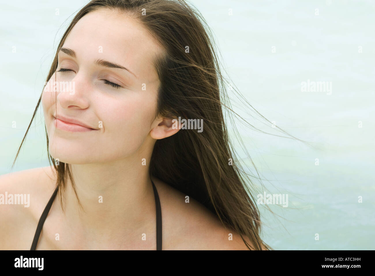 Young woman outdoors with eyes closed, hair tousled by breeze, close-up - Stock Image