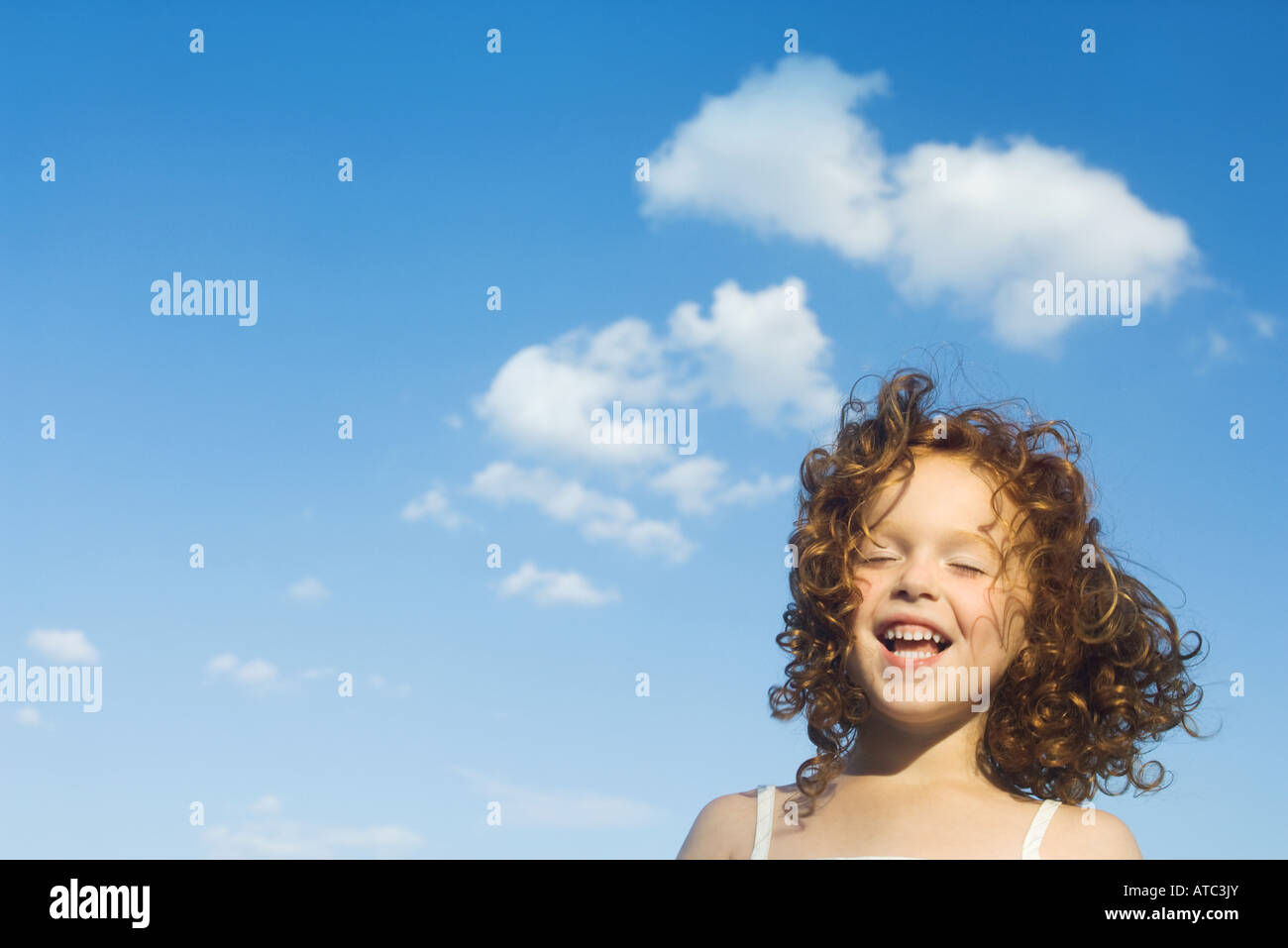 Little outdoors with tousled hair, eyes closed, smiling - Stock Image
