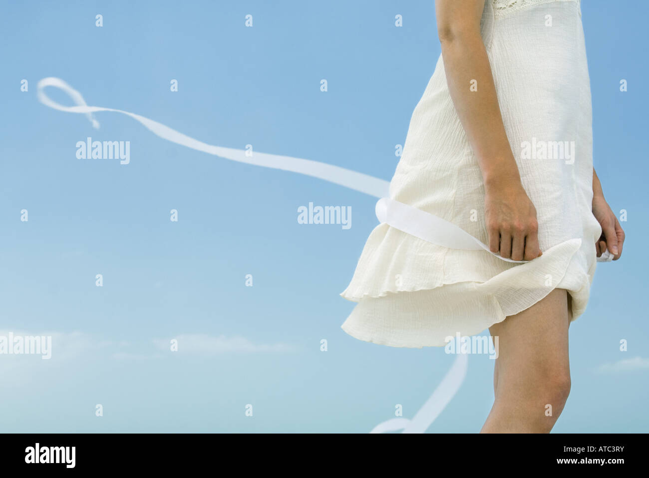 Woman in dress holding ribbon, tousled by wind, cropped view - Stock Image