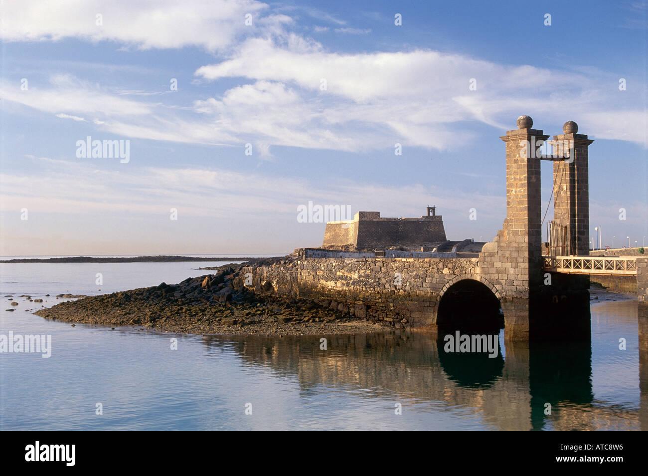 The 16th century Puente de las Bolas with Castillo de San Gabriel in the background beyond the waters off Arrecife Stock Photo