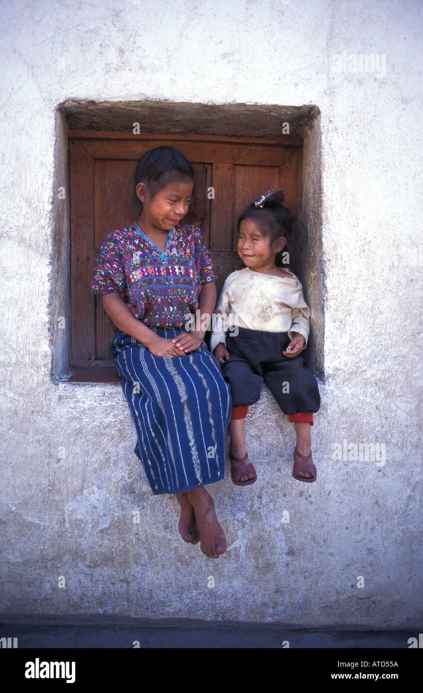 Young sisters seated in a window Tzutihil Maya community San Lucas Toliman Guatemala - Stock Image