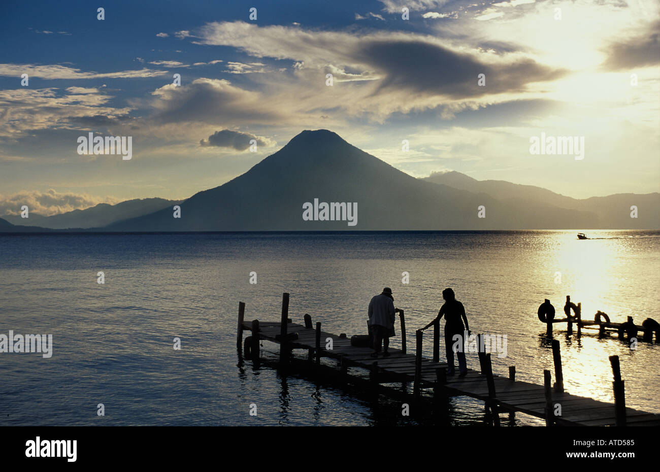 Tourists at the end of a jetty silhouetted at sunset Panajachel Lake Atitlan Guatemala San Pedro volcano beyond - Stock Image