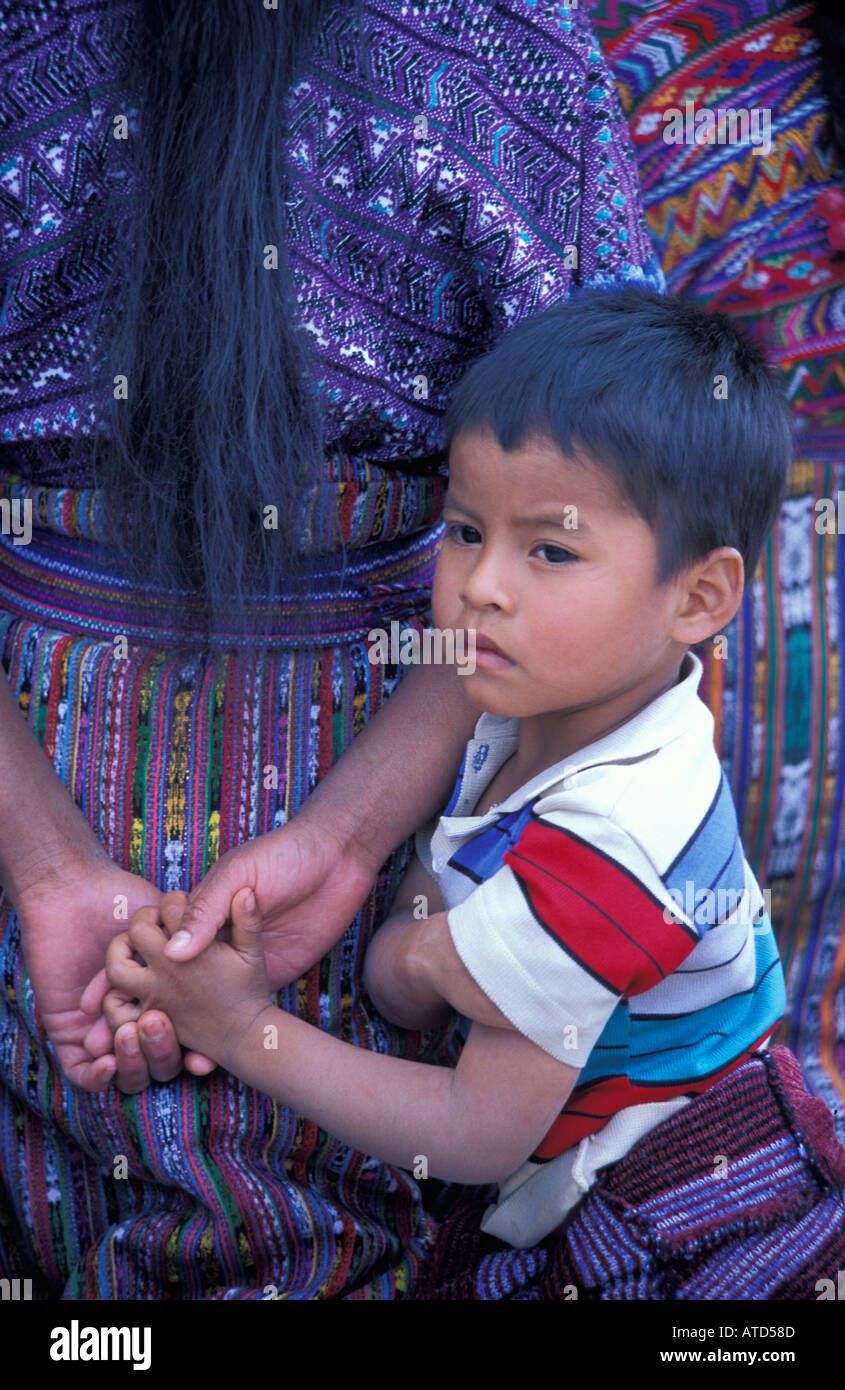 boy holding hands of mother San Martin Jilotepeque Guatemala - Stock Image