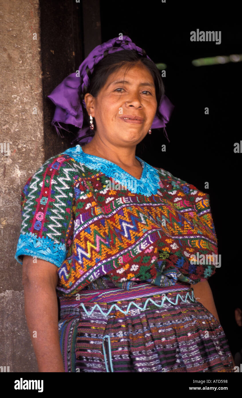 Friendly woman from San Martin Jilotepeque in brocaded blouse standing in the doorway to her home Guatemala - Stock Image