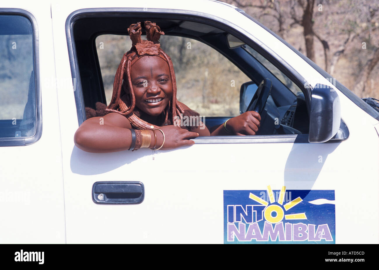 Himba woman Distinctive hair decoration and adornments At the wheel of a 4x4 Kaokoveld S of Opuwo Namibia - Stock Image