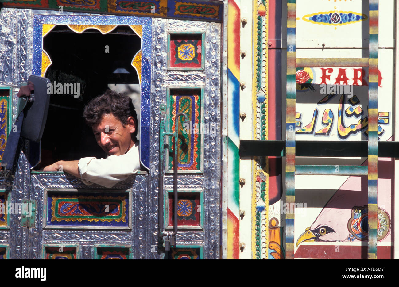 Seated in his decorated cab a friendly Pakistani truck driver on the Karakoram Highway to China Pakistan - Stock Image