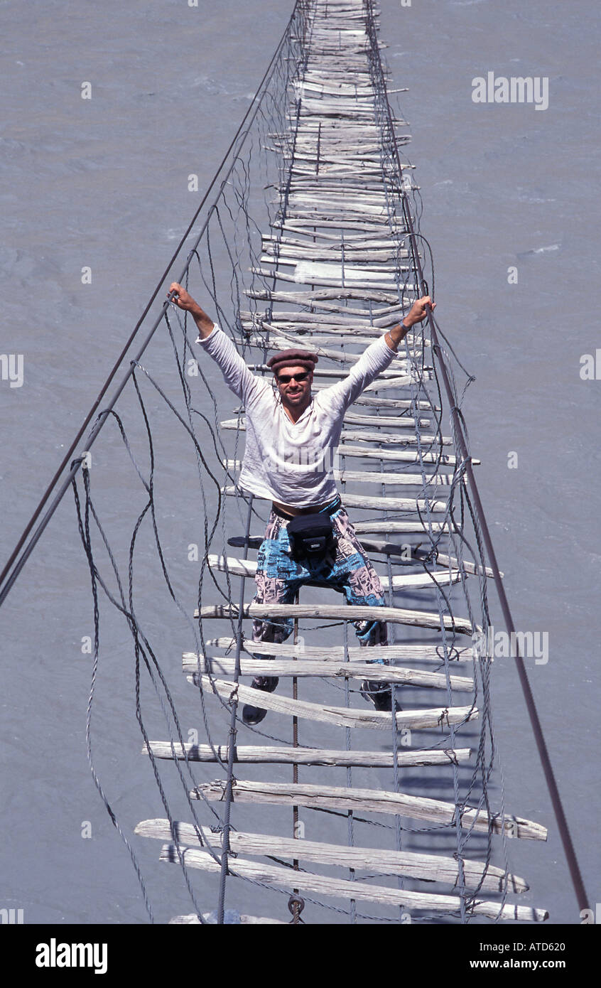 Intrepid traveller crossing the Hunza river on suspended footbridge Trekking nr Passu Karakoram Highway N Pakistan - Stock Image