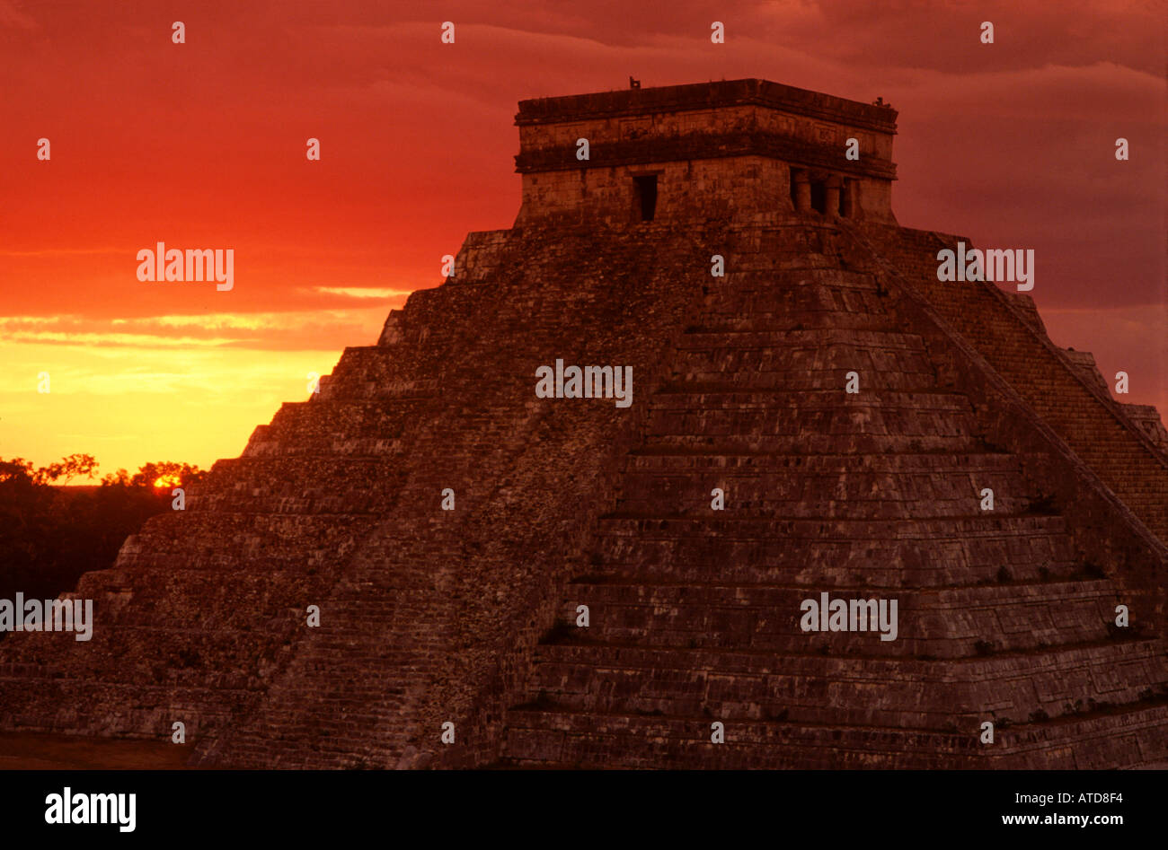 The sun sets behind the Pyramid At Chichen Itza on the Yucatan Peninsula of Mexico is silhouetted against the brilliant colors - Stock Image