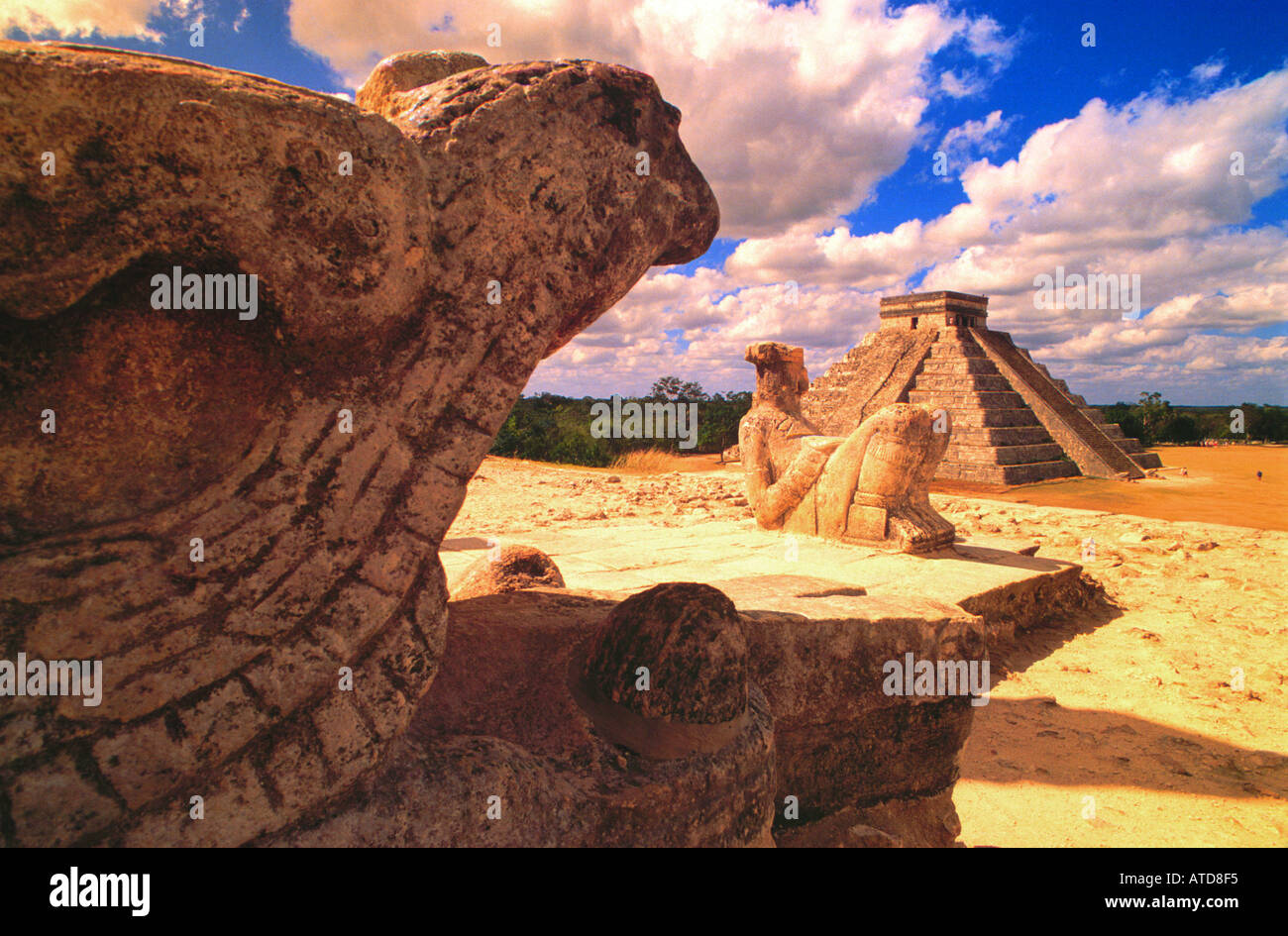 Statues of gods and reptiles sit upon the ruins of Chichen Itza with a view of El Castillo or the Pyramid in the distance - Stock Image