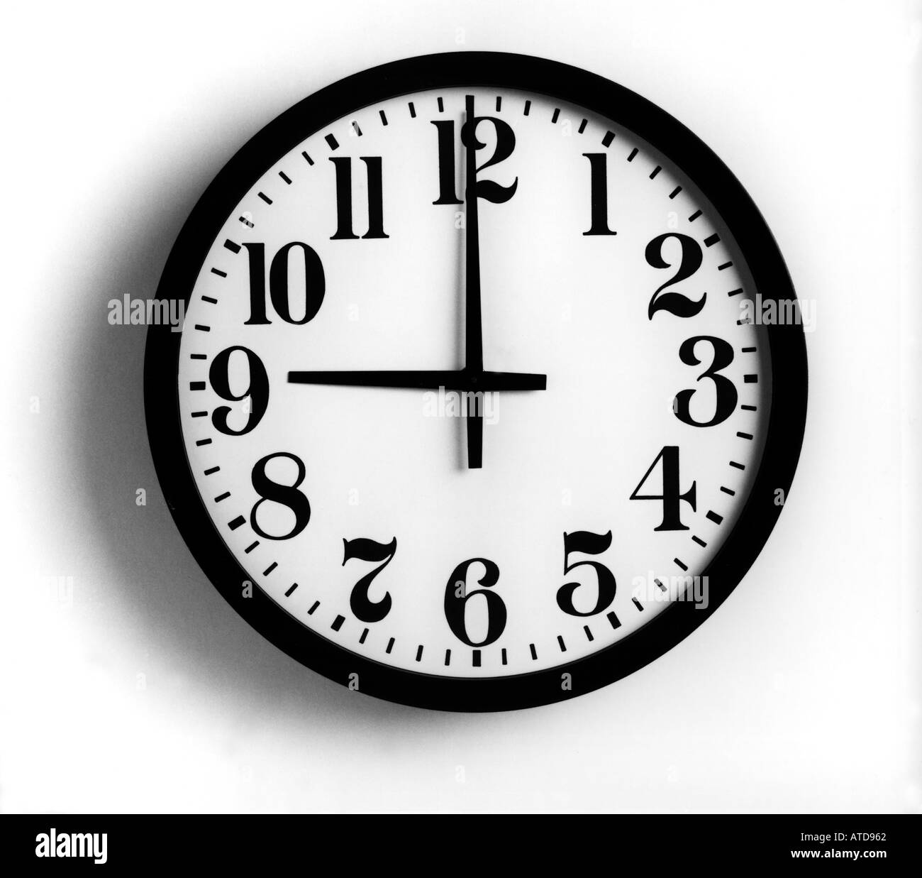 A black and white image of a clock on a white wall showing nine o clock - Stock Image