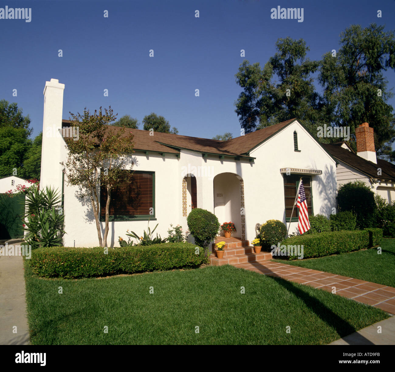 Single story white stucco house with a red tile roof palm tree and american flag