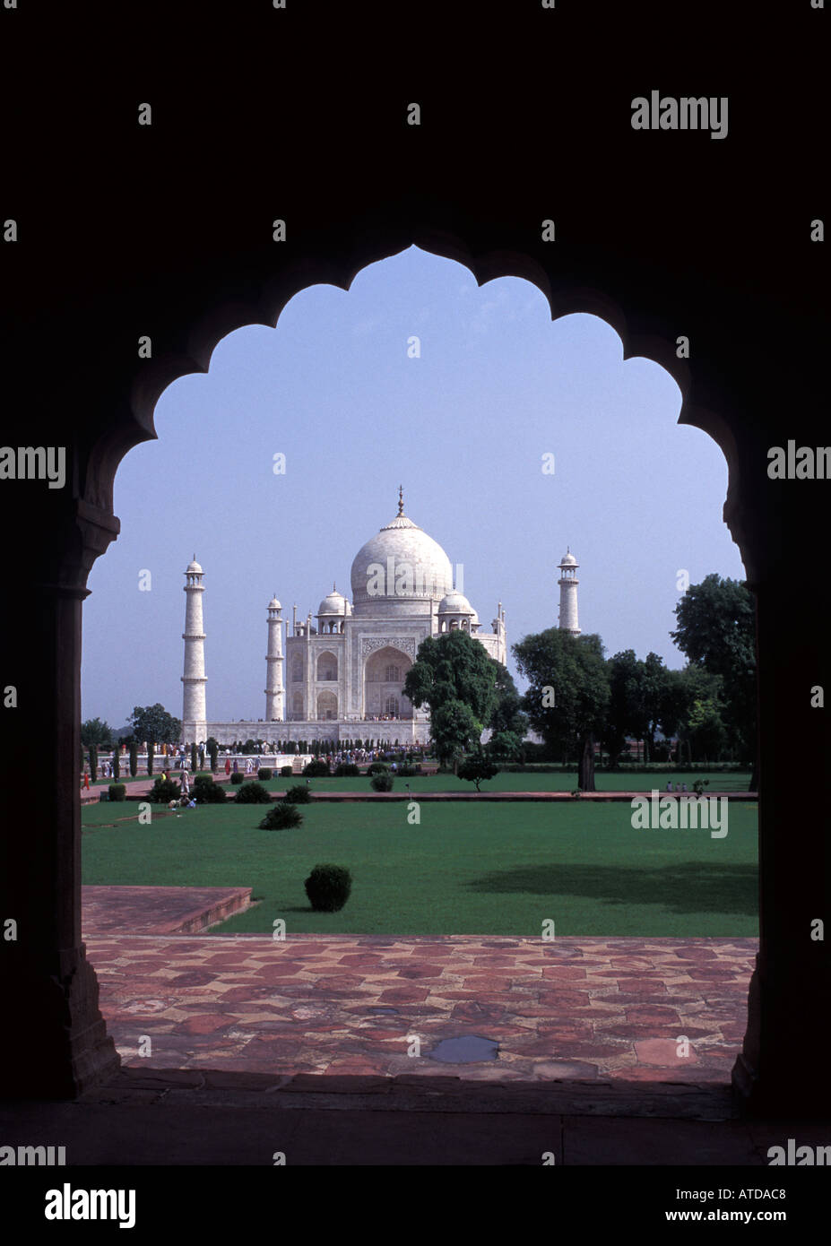 Taj Mahal framed by the scalloped archway of the corridor to the side of the entrance gateway Agra India - Stock Image