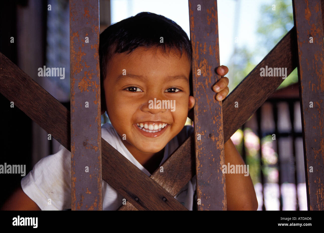 Malaysian boy grins from behind a wooden gate Penang Malaysia - Stock Image