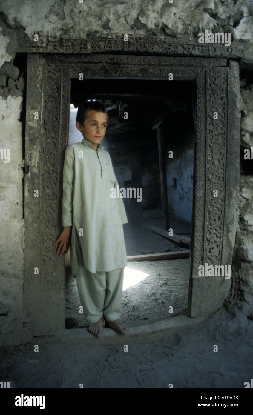Pakistani boy from the Hunza valley photographed in a doorway at Altit Fort Karimabad - Stock Image