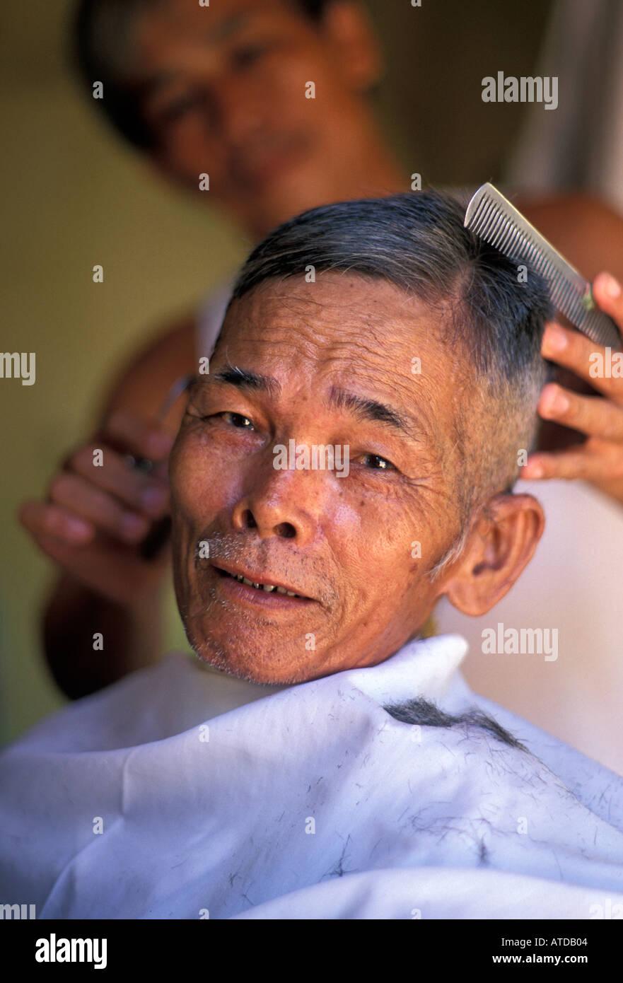 Vietnamese man getting his hair cut Local hairdressers on Ng Thi Minh Khai Street Hoi An Vietnam - Stock Image