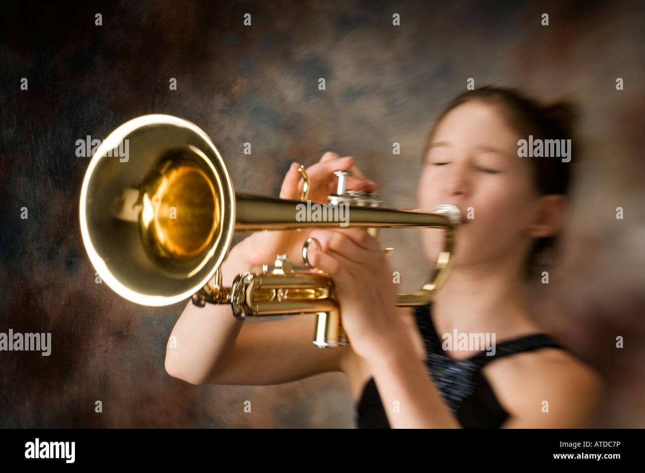 young pre teen girl female woman blowing playing trumpet music instrument with passion and emotion - Stock Image