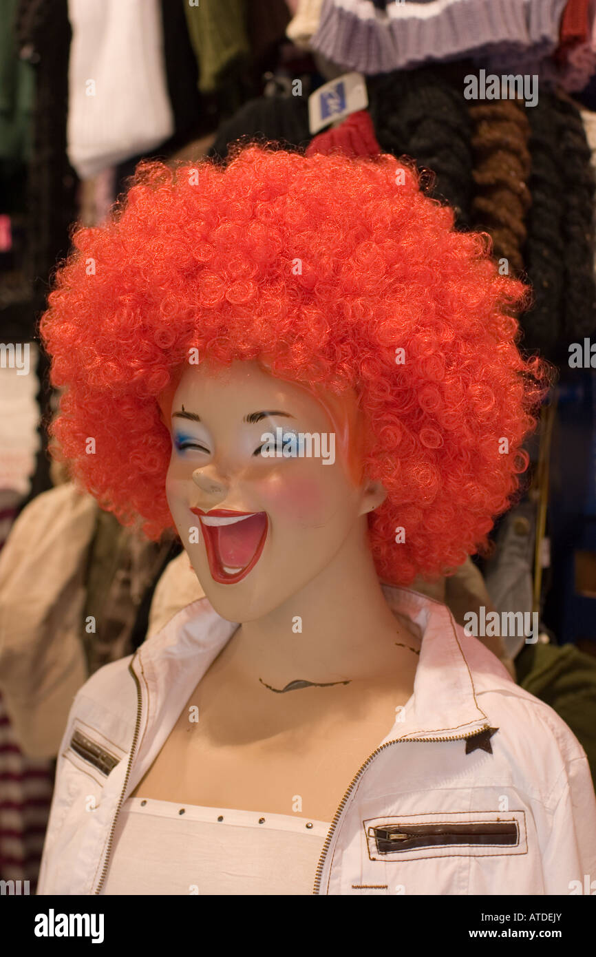 laughing shop window dummy with red wig - Stock Image
