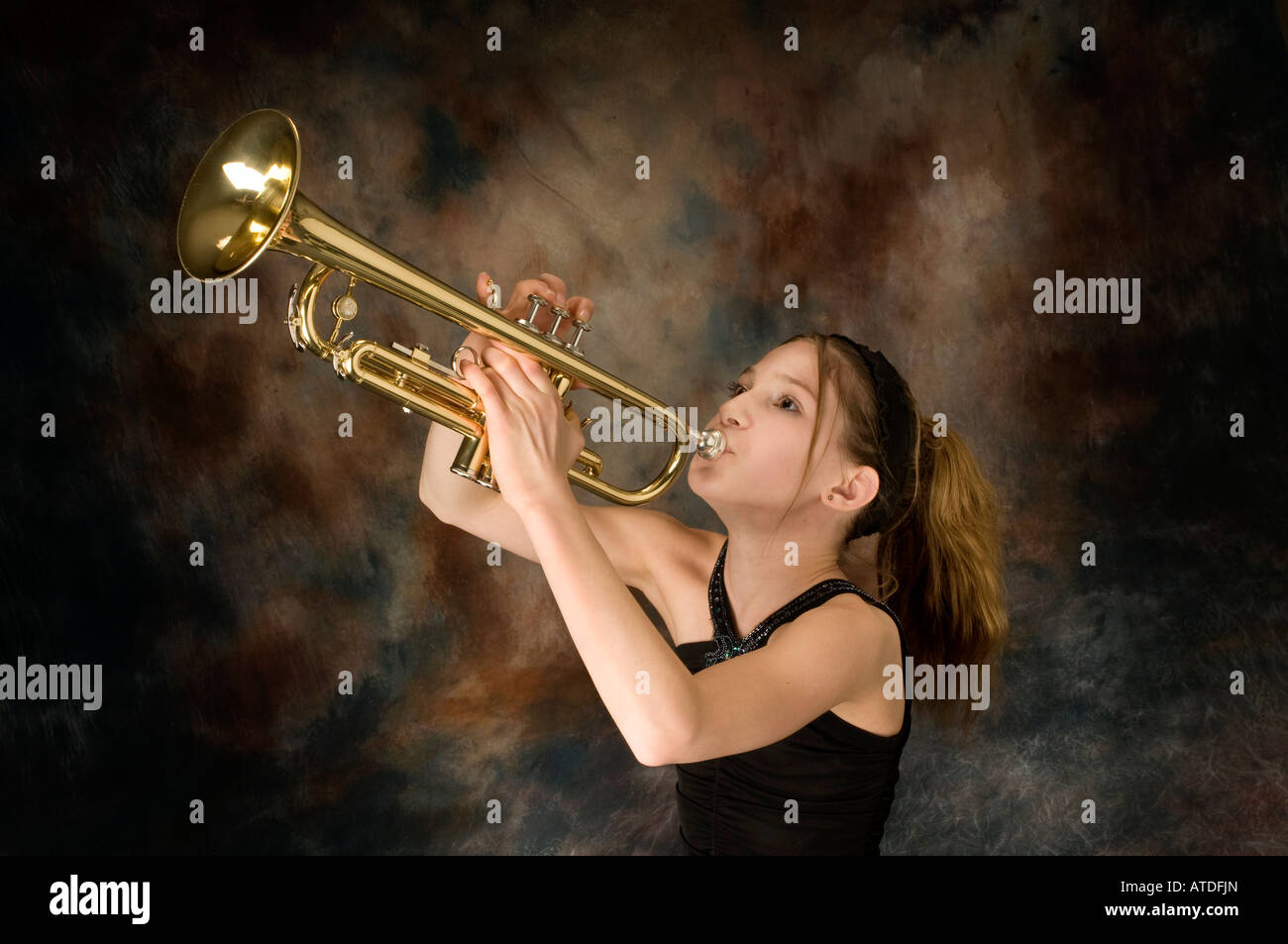 Young female student posing with trumpet - Stock Image