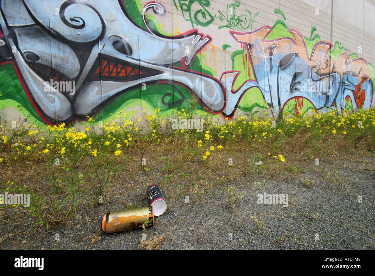 Empty color-can in front of a concrete wall with colorfull graffitti - Stock Image