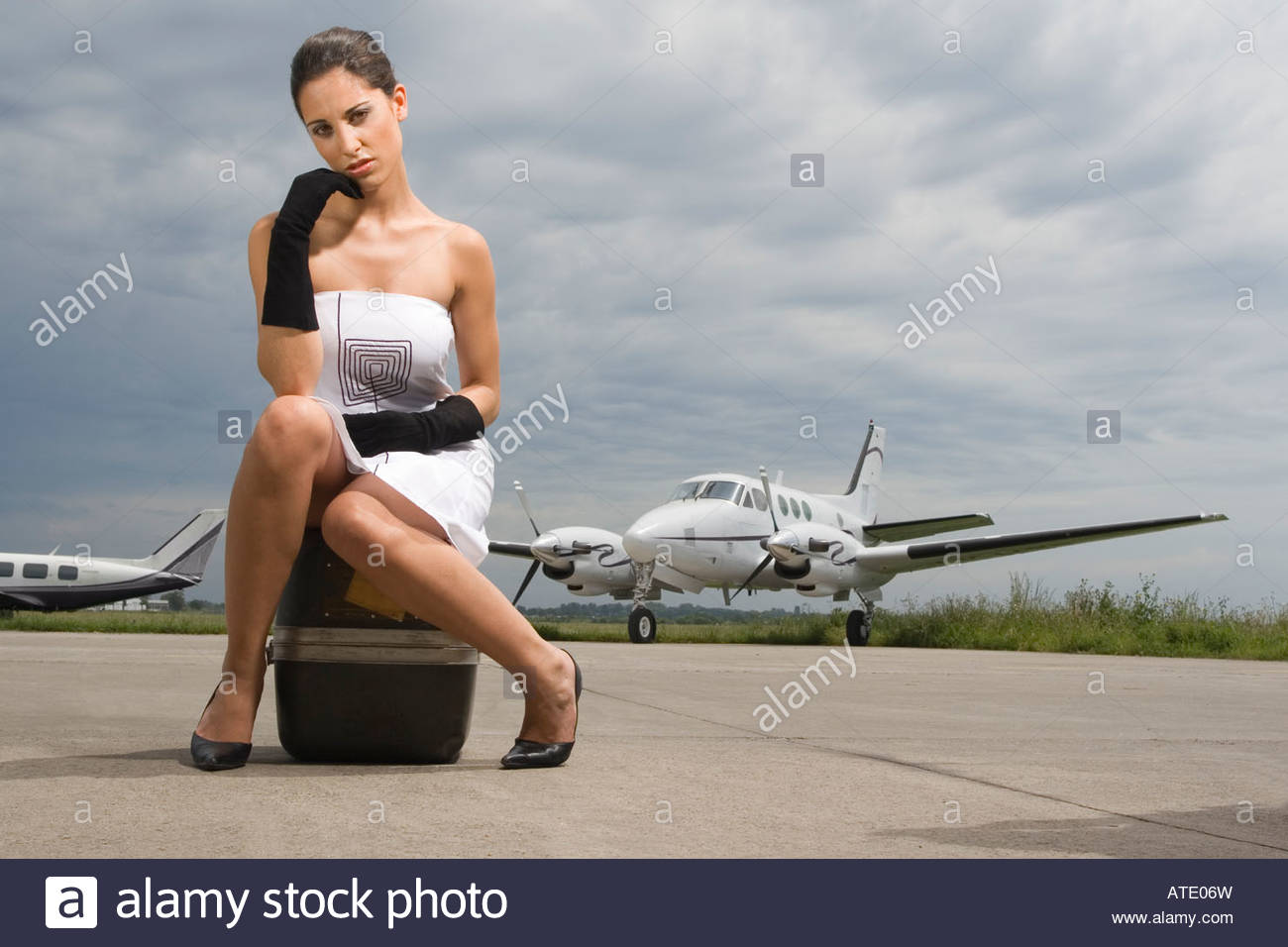 Portrait of a young woman sitting on her luggage at an airport - Stock Image