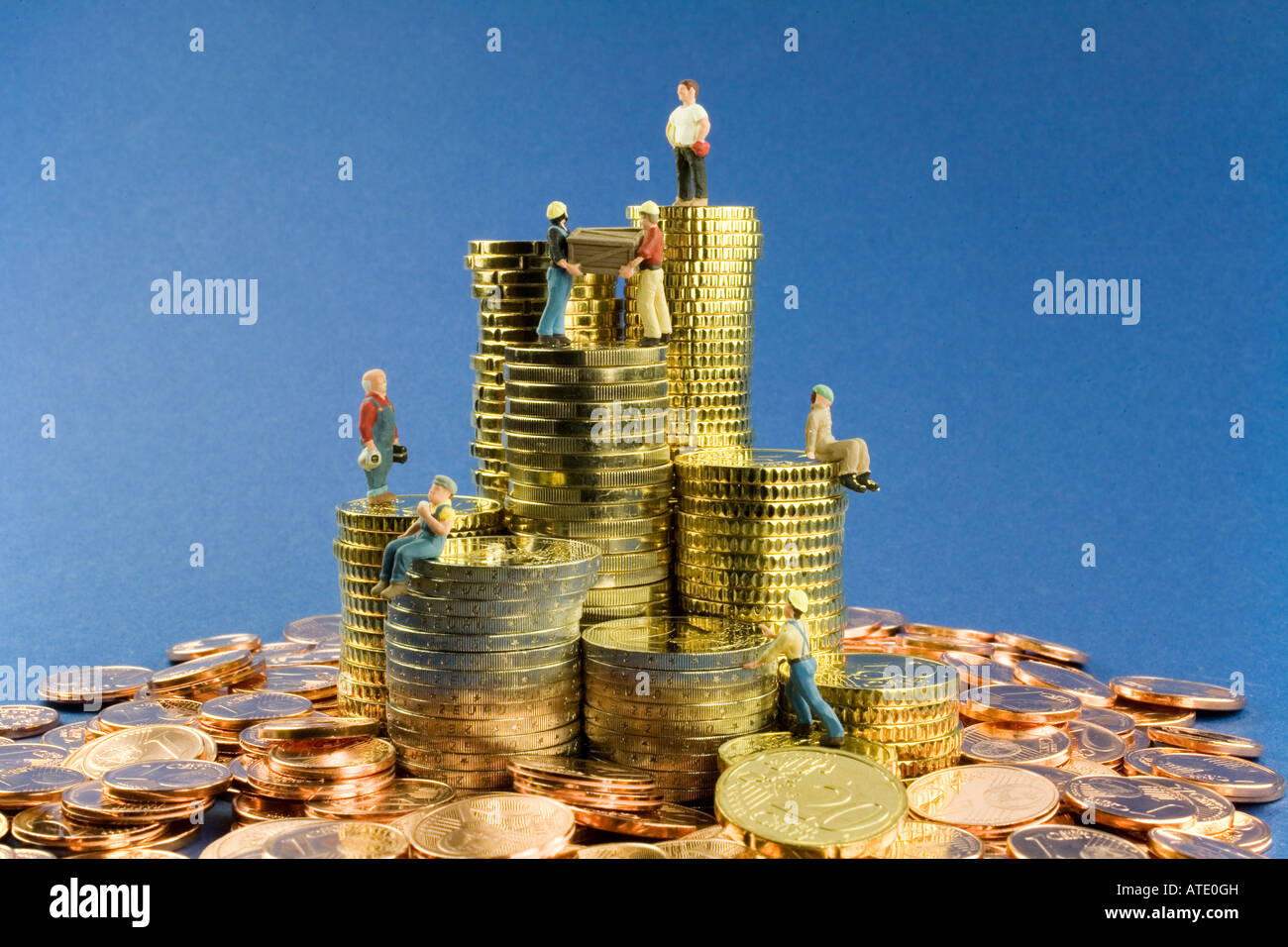 Building worker figures on heaps of money and money piles - Stock Image