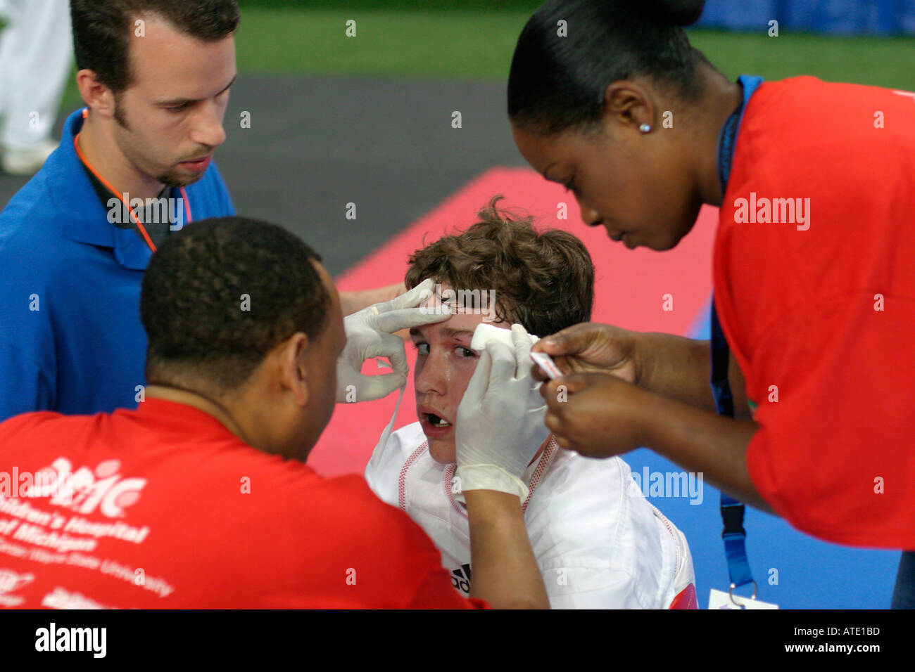 A trainer checks a boy s injury during the AAU Junior Olympics in Detroit - Stock Image